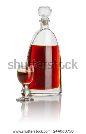 Carafe and glass goblet filled with brown liquid - stock photo