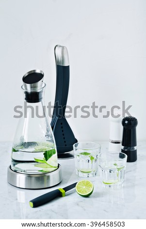 Carafe and two glasses of water with lemons and mint