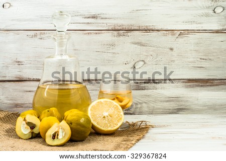 Carafe of alcohol tincture and glass of drink with quince fruits, vintage photo. - stock photo