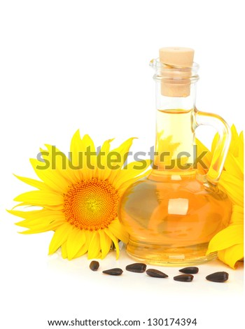 Carafe with vegetable oil and sunflowers isolated on the white background - stock photo