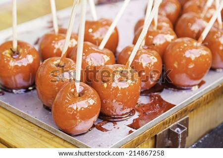 Caramel apples on a fair, detail of a sweet wooden stick - stock photo