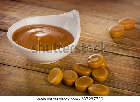Caramel candies and sauce on  wooden background. Selective focus - stock photo