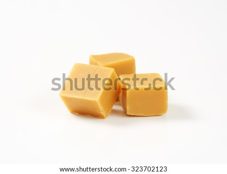 Caramel candies on white background