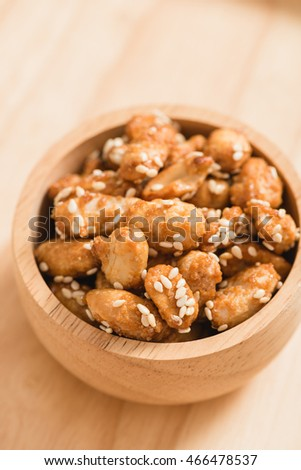 Caramel Coated Peanut with Sesame on Wooden Background
