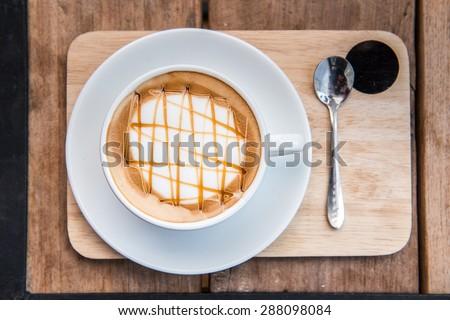 caramel macchiato on wood table - stock photo