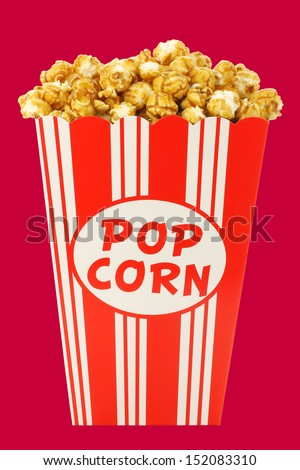caramel popcorn in a decorative paper popcorn cup isolated on a red background