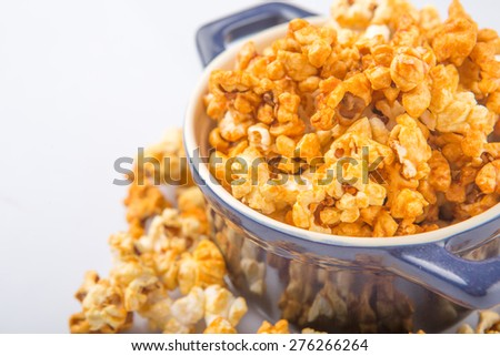 Caramel popcorn in blue pot over white background
