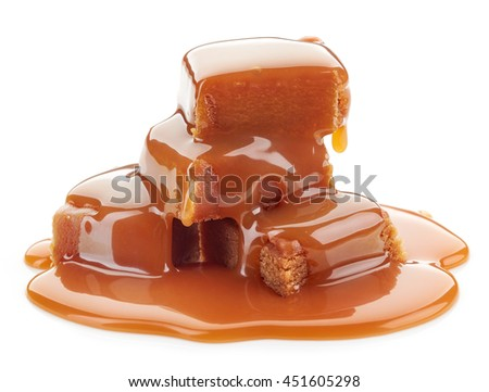 caramel sauce flowing on caramel candies, isolated on white background