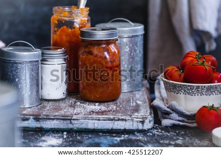 Caramel tomatoes jam or sauce in glass jars. Rustic dark style.