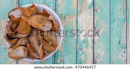 Caramelized cloves of black garlic in white bowl over wooden background