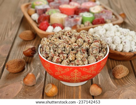 Caramelized peanuts with sesame in a red bowl on a brown background
