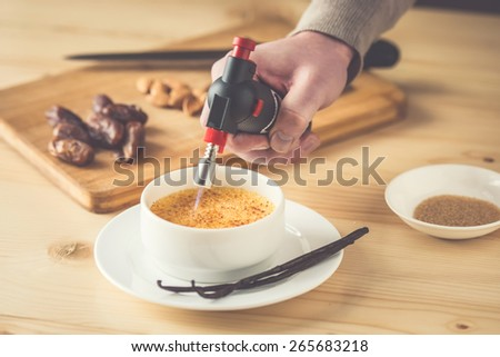 Caramelizing of creme brulee with bourbon vanilla sticks and hand with torch. Toned picture - stock photo