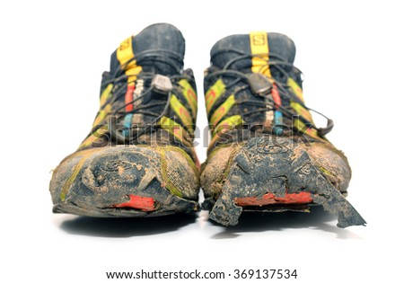 Caransebes, Romania - January 27, 2016: A pair of worn, ripped and dirty Salomon trail running shoes over white background. Shot taken on January 27th 2016.  - stock photo
