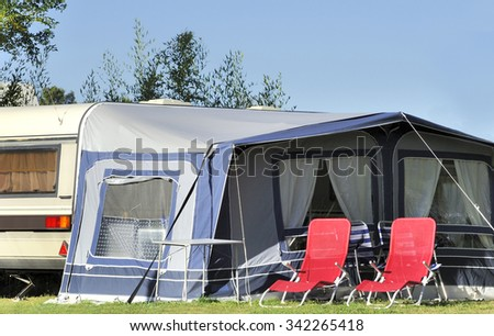 Caravan at a camp site with at front of the tent two red camping chairs - stock photo