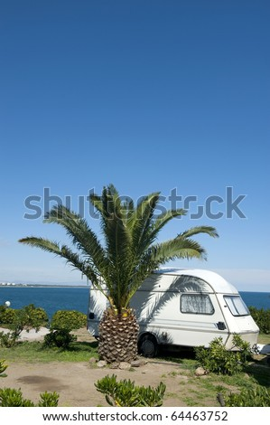 Caravan next to a palm tree with at the background the sea. SPACE FOR TEXT AT TOP