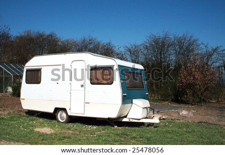 Caravan parked at caravan or camping site. white leisure home on lawn - stock photo