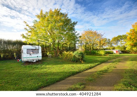 Caravan trailer on a green lawn under the trees in camping, on a sunny Autumn day in France - stock photo