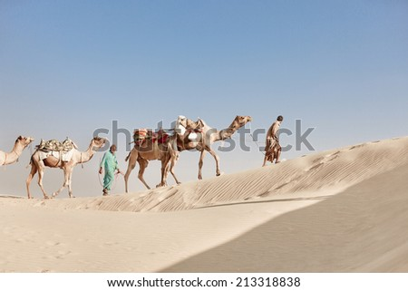 Caravan with bedouins and camels in white sand dunes under blue sky - stock photo