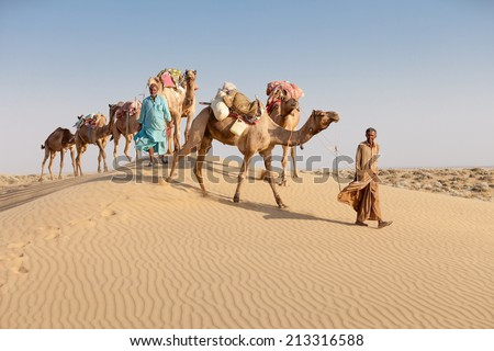 Caravan with bedouins and camels on sand dunes in desert at sunset. Thar desert or Great Indian desert. - stock photo