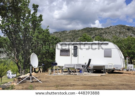 Caravan with satellite dish and barbecue at a camping surrounded with mountains