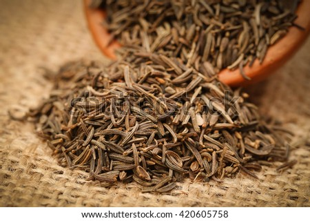 Caraway seeds in a bowl on jute - stock photo