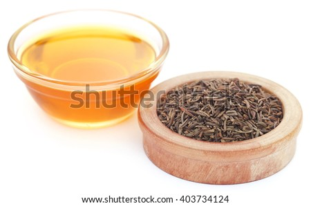 Caraway seeds with essential oil in glass bowl over white background