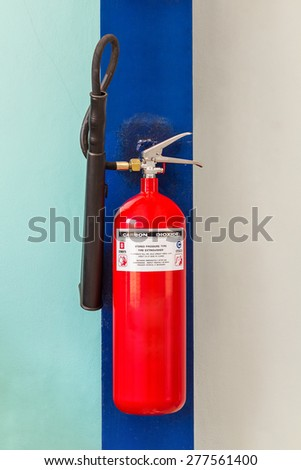 Carbon dioxide fire extinguisher on factory wall - stock photo
