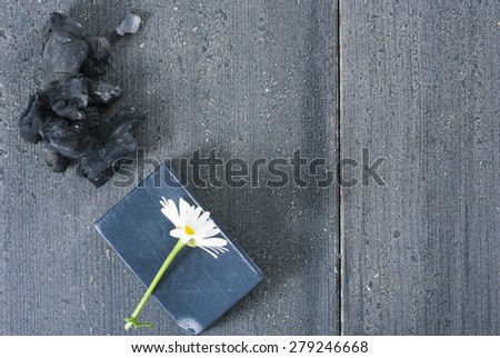 carbon soap with white flower and a pile of coal on old black wooden table