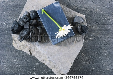 carbon soap with white flower and a pile of coal on stone, old black wooden table background - stock photo