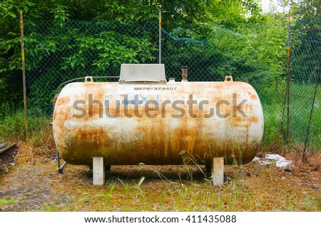 CARBONARA DI PO, ITALY - APRIL 23, 2016: Old dirty gas tank standing outdoors - stock photo