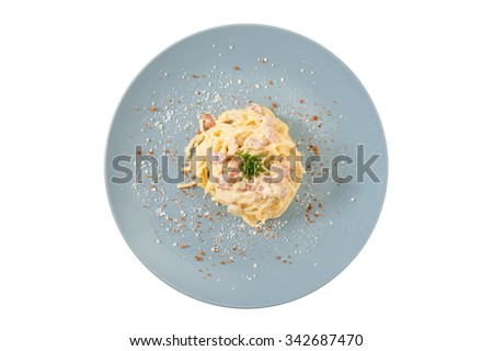 Carbonara pasta with bacon in grey ceramic dish isolated on white background with clipping path - stock photo