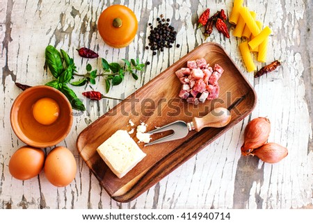 carbonara raw ingredients over white wooden table