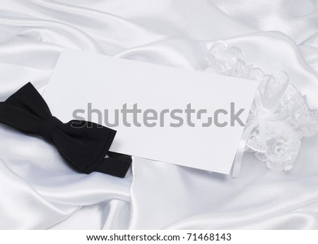 Card, bridal garter and bow  on a background white silk