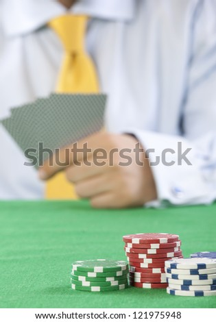card player with yellow tie  gambling casino chips on green felt background selective focus - stock photo