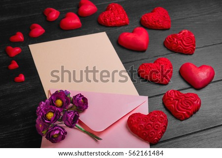 Card to Valentine's Day. Envelope with paper for text congratulations letter. Bouquet flowers on envelope. Heart from red marzipan. Heart with pattern and heart sleek black wooden background
