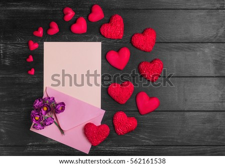 Card to Valentine's Day. Envelope with paper for text congratulations letter. Bouquet flowers on envelope. Heart from red marzipan. Heart with pattern and heart sleek black wooden background.Top view