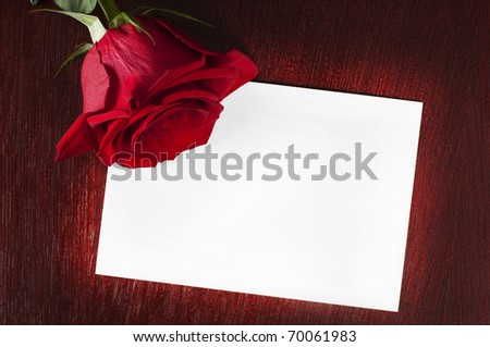 card with a red rose on the wooden table - stock photo
