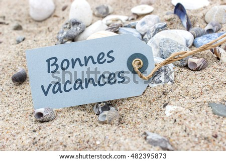 "Card with French words ""Nice Vacations"" in beach sand / Beautiful Vacations / beach holiday"