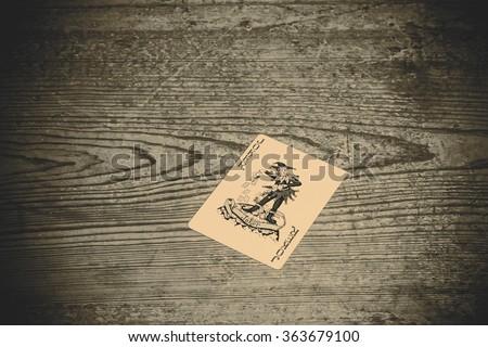 card with joker on the wooden floor - stock photo