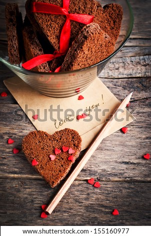 Card with Message Love You on the Letter and Chocolate Cookies in Shape of Heart at Valentine Day
