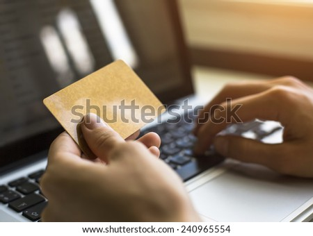 Card (with place for your text) in hand and entering security code using laptop keyboard. - stock photo