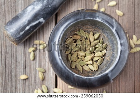 Cardamom green seeds superfood ayurveda aroma spice in a mortar with pestle - stock photo