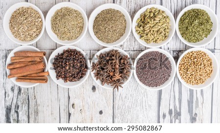 Cardamom, star anise, cinnamon, clove, coriander seed spices and parsley, thyme, rosemary herbs in white bowls over weathered wooden background