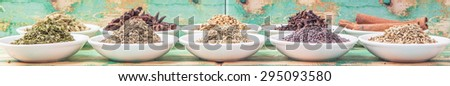 Cardamom, star anise, cinnamon, clove, coriander seed spices and parsley, thyme, rosemary herbs in white bowls over weathered wooden background - stock photo