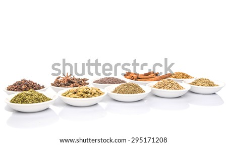 Cardamom, star anise, cinnamon, clove, coriander seed spices and parsley, thyme, rosemary herbs in white bowls over white background - stock photo