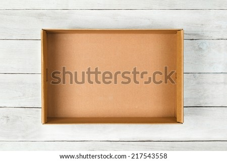 Cardboard box on a white wooden background - stock photo