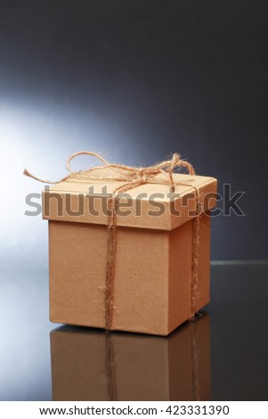 Cardboard box tied with twine on dark background - stock photo