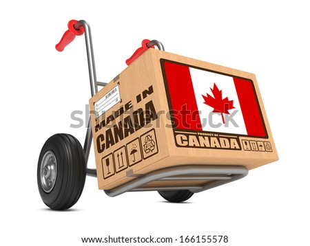 Cardboard Box with Flag of Canada and Made in Canada Slogan on Hand Truck White Background. Free Shipping Concept. - stock photo