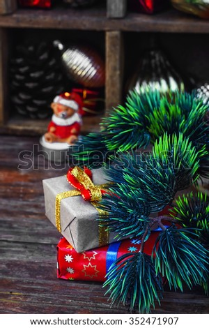 Cardboard box with gift on background of box with Christmas decorations.