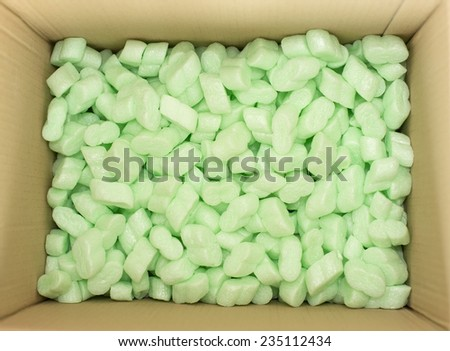 cardboard box with green packing foam pellets top view - stock photo